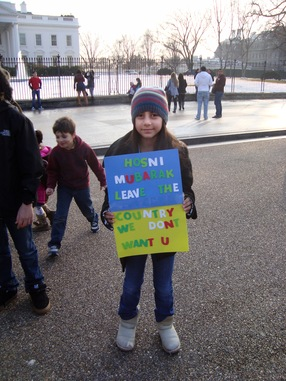 A girl holds a sign reading: 'Hosni Mubarak/leave the country/We don't want U; NewsHour photo by Mila Sanina