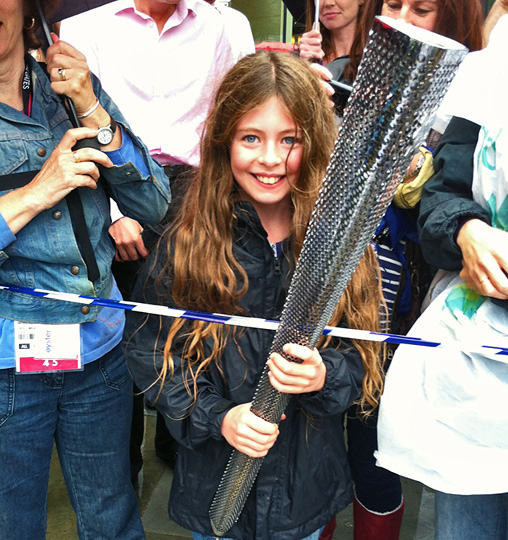 Young girl holds extinguished torch.