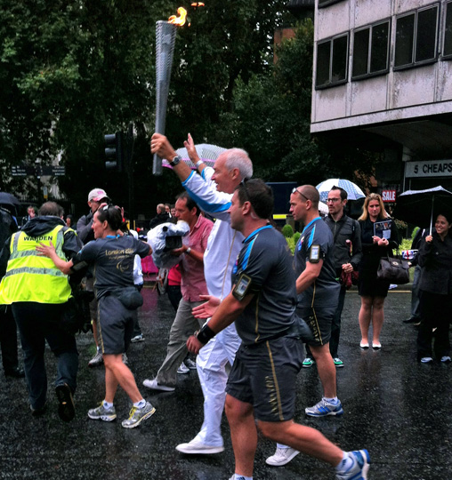 John Snow carrying torch past St. Paul's Cathedral in London.