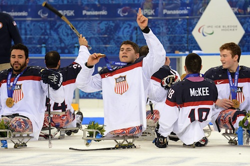 Sled hockey player Brody Roybal celebrates with his gold medal after the medal ceremony.