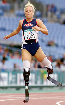 Woman sprinter wearing modern prosthetic legs