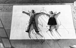 "Charles and Ray Eames ""pinned"" by chair bases, 1947. © 2011 Eames Office, LLC."
