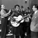 Sister Rosetta Tharpe recording at Decca Records with bandleader Lucky Millinder (left) and manager Moe Gale (right) in 1941. Photo Credit: Photo taken by Charles Peterson. Courtesy Don Peterson.