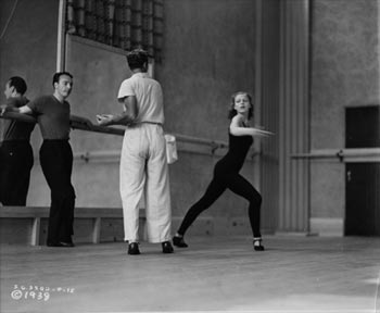 George Balanchine leaning against a ballet bar during rehearsal.