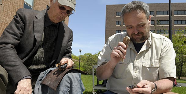 Alan Alda and John Shea work on stone tools side by side. Photo: © Larry Engel 2008