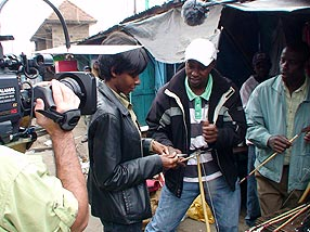 Veronica became the center of attention at the Kariokor Market in Nairobi when she showed up with our film crew. Here a vendor exhibits the modern arrows he sells there. Caption: Maggie Villiger