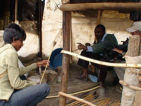 Veronica examines the arrows of a modern hunter in Kenya while the Human Spark camera captures their exchange. Credit: Maggie Villiger