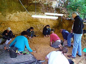 The Human Spark crew films the excavation team hard at work in the rock shelter. Credit: Maggie Villiger