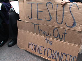 "A protester holds a sign at the Occupy Wall Street protests in New York City: ""Jesus Threw Out the Moneychangers"""