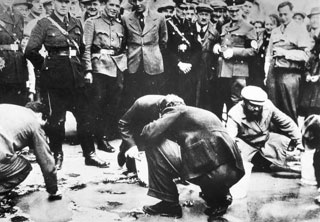 The national community: Austrian Nazis and local residents look on as Jews are forced on hands and knees to scrub pavement, Vienna, Austria, March-April 1938