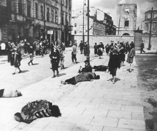 Pedestrians in the Warsaw Ghetto walk past corpses lying on the pavement on Rynkowa Street, near the ghetto wall, Warsaw, Poland, 1940-1941.