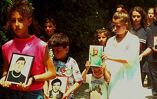 Family members of the Cuska victims carry photographs of the deceased in a funeral procession. © 1999 Fred Abrahams/Human Rights Watch