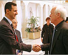 Bashar Al-Assad shakes hands with series editor Stephen Talbot.