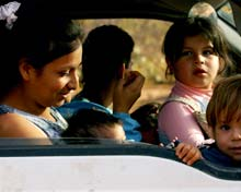 Women and children in front seat of a truck.