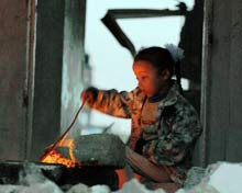 Child by a makeshift fire.