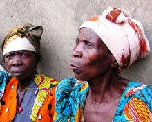Two Congolese women watch ballots being unloaded with folded arms.