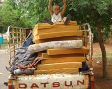 Child on top of truck piled with possessions.