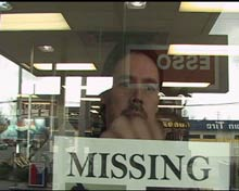 Father pins missing person poster on a gas station window.