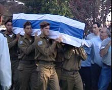 Men carry coffin draped in Israeli flag.