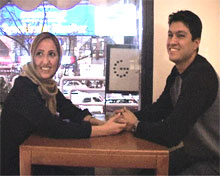 A smiling Iranian couple sitting in a cafe
