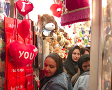 Iranian women jostle through the doorway of a Valentine's Day gift store
