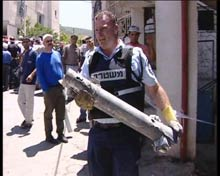 Policeman holds rocket fired by Hezbollah in the village of Piqiin.