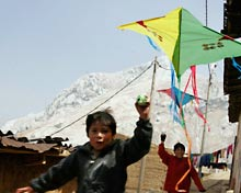 Children run with kites.