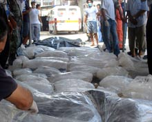 Bodies wrapped in plastic are lined up outside a hospital.