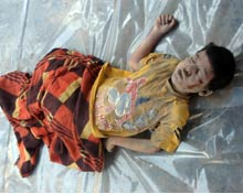 Body of dead child layed out on plastic sheeting.