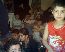 Refugees crowded in room.