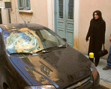 A woman stands in the street by a car with a smashed windshield