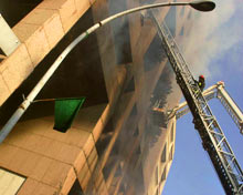 A firefighter battles a building fire atop a firetruck ladder