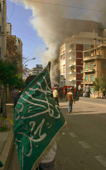 A man stands wrapped in a green Islamic flag watching a building burn