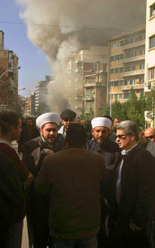 A crowd of men stand watching a burning building