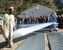 Men carry corrugated sheets of metal.