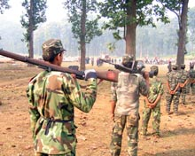 Maoist soldiers march in forest clearing.
