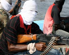Nigerian militia men with automatic weapons in boat.