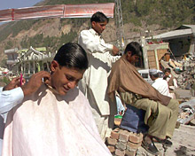 Young men cut hair amongst the rubble.