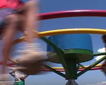 A child spins around a colorful merry go-round.