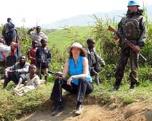 Reporter Suzanne Marmion sits on the side of a dirt road, with armed soldier standing behind her.