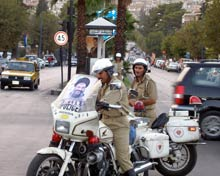 Traffic police on motorbikes parked at a busy intersection.