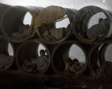 young children take refuge from the rain inside large construction pipes.