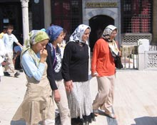 young women in streets wearing headscarves.