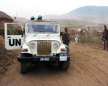 A Unite Nations jeep is parked along a remote dirt road.