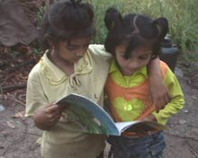 Two children share reading a book.