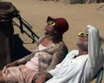 A couple in the desert looks toward the eclipse wearing special eyewear.