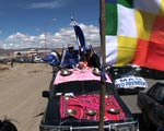 Vehicles with flags travel through Bolivia's high plateau.