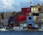 Colorful houses line the waterfront of Lampedusa.