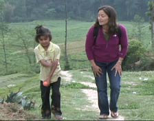 The reporter and young child trek up hillside.