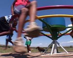 Children spinning on play pump wheel.